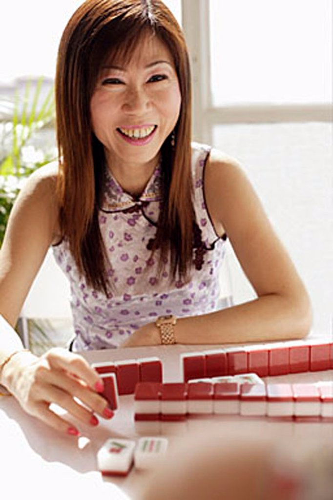 Woman smiling, mahjong tiles in front of her : Stock Photo