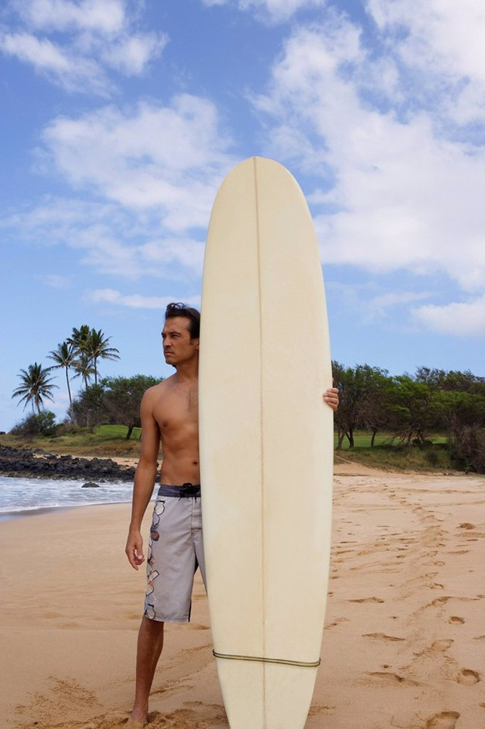 man standing on beach with surf board : Stock Photo