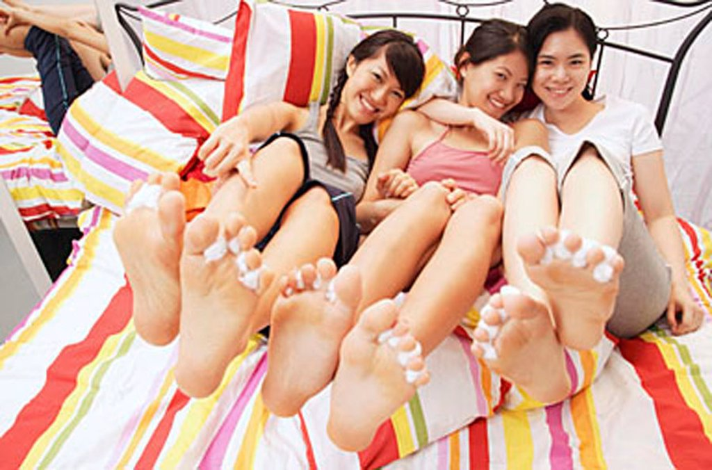 Three young women sitting on bed, showing their feet to camera : Stock Photo