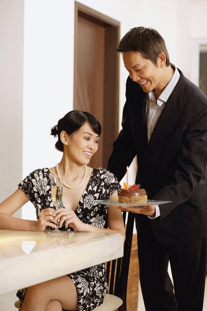 Woman sitting at table, man serving her a cake : Stock Photo