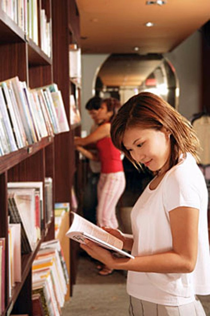 Young woman at bookstore, reading book : Stock Photo