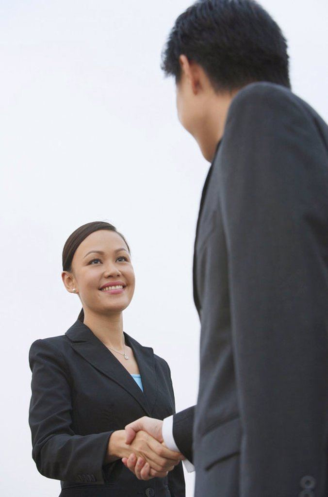 Businessman and businesswoman shaking hands, low angle view : Stock Photo