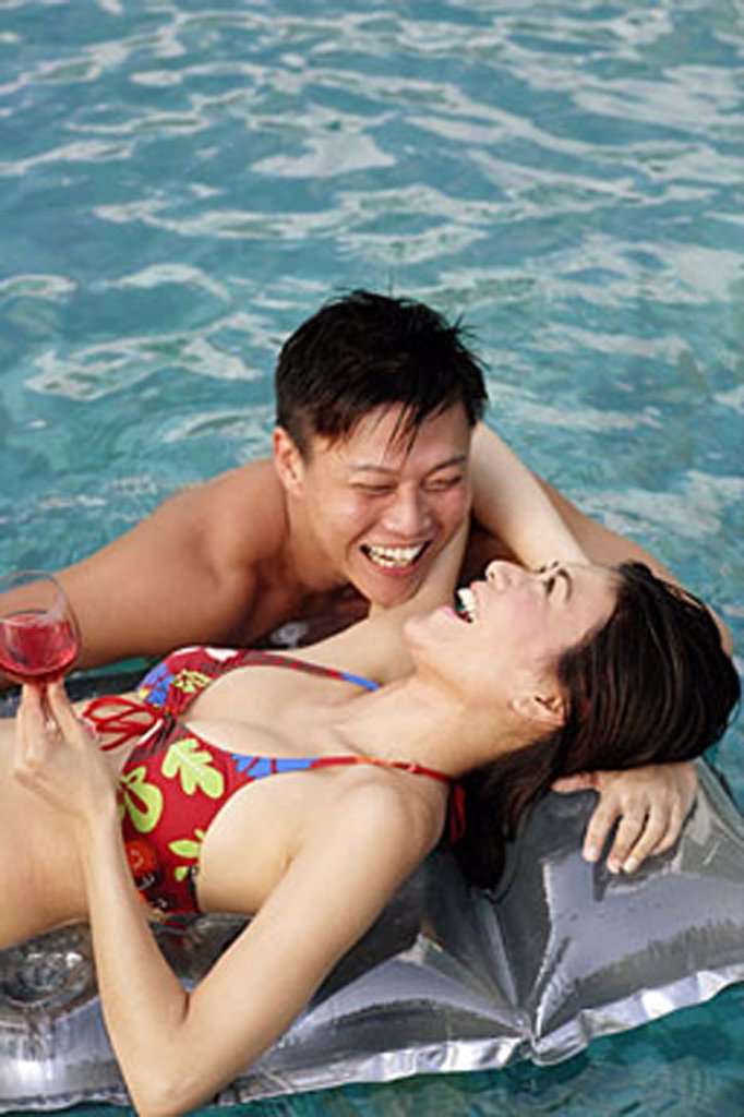 Woman on pool raft, man floating in water next to her : Stock Photo