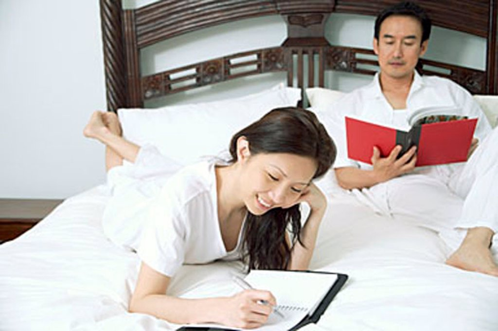 Couple in bedroom, woman writing in diary, man reading book : Stock Photo