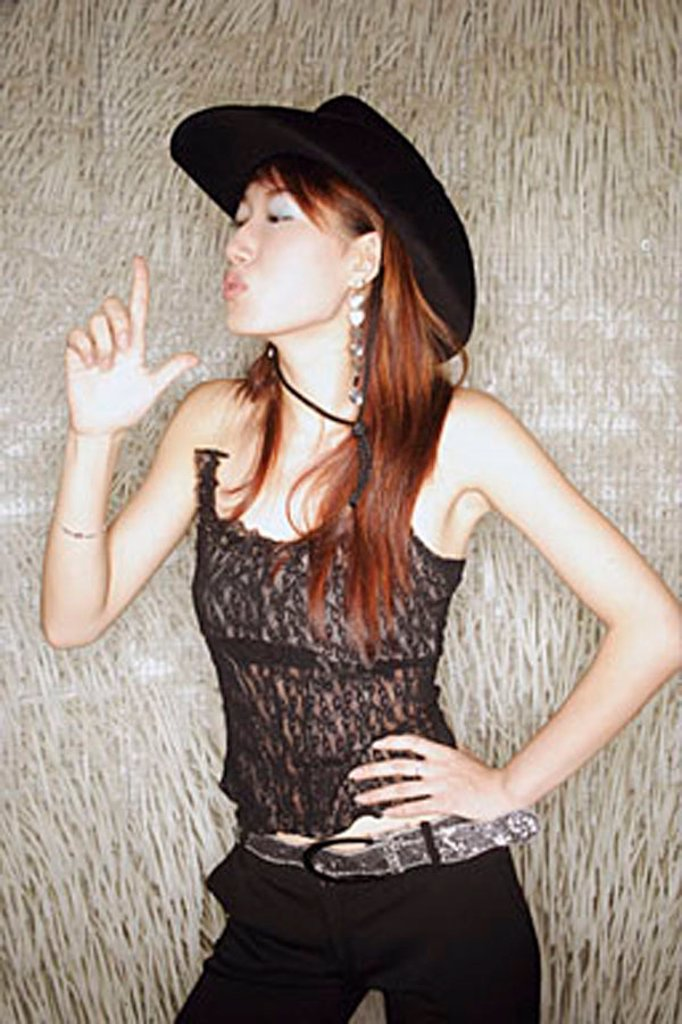 Young woman, hands on hip, wearing cowboy hat : Stock Photo