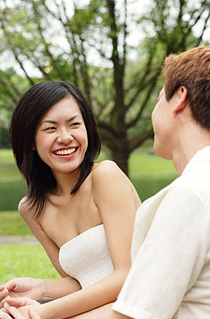 Woman smiling at man sitting next to her : Stock Photo