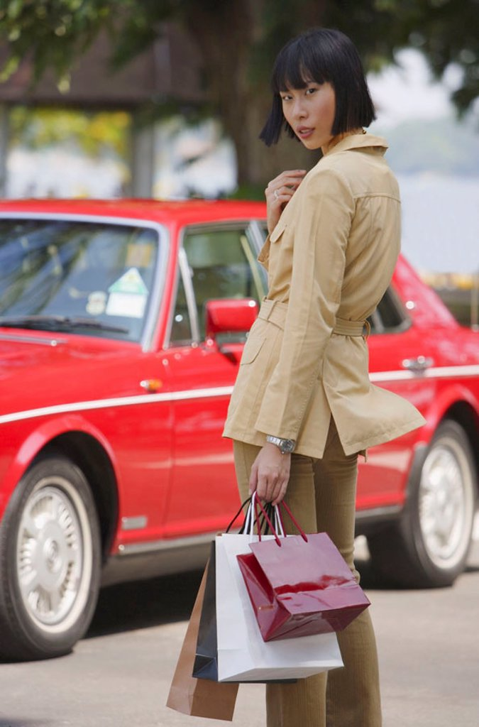 Woman with shopping bags, turning to look at camera, car in the background : Stock Photo