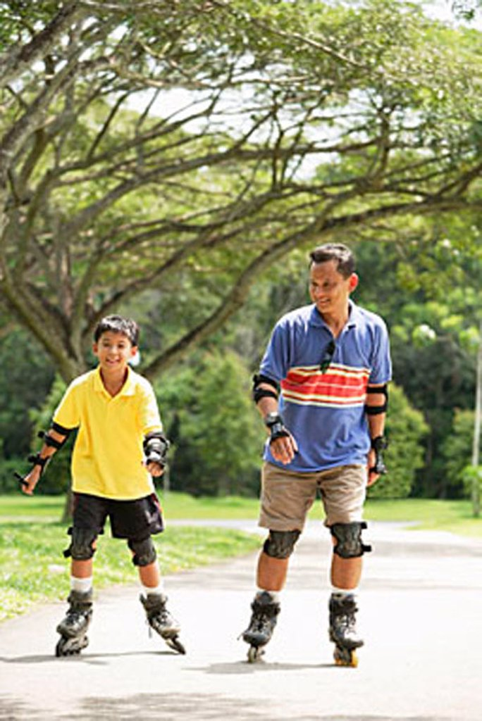 Stock Photo: 4065-12612 Father and son in park, on roller blades