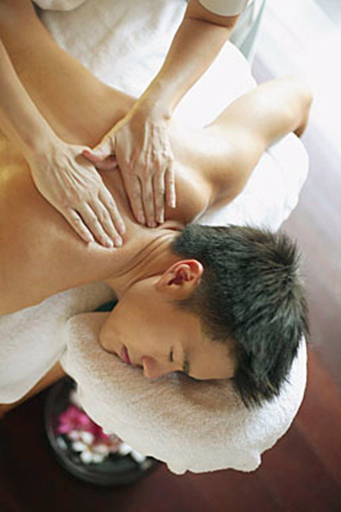Young man receiving back massage : Stock Photo