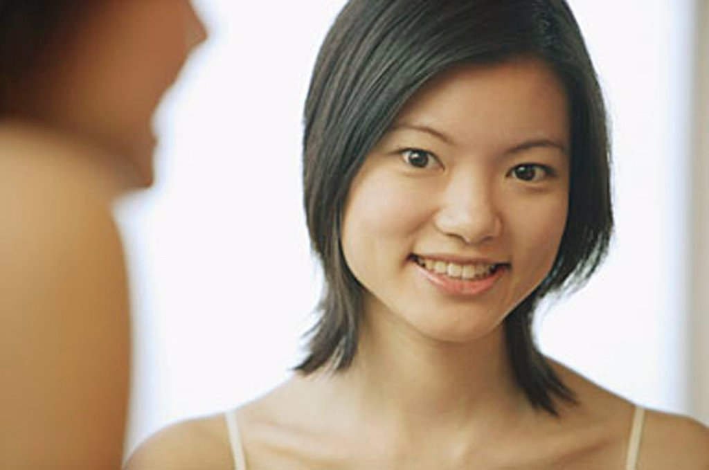 Young woman looking at camera, toothy smile : Stock Photo