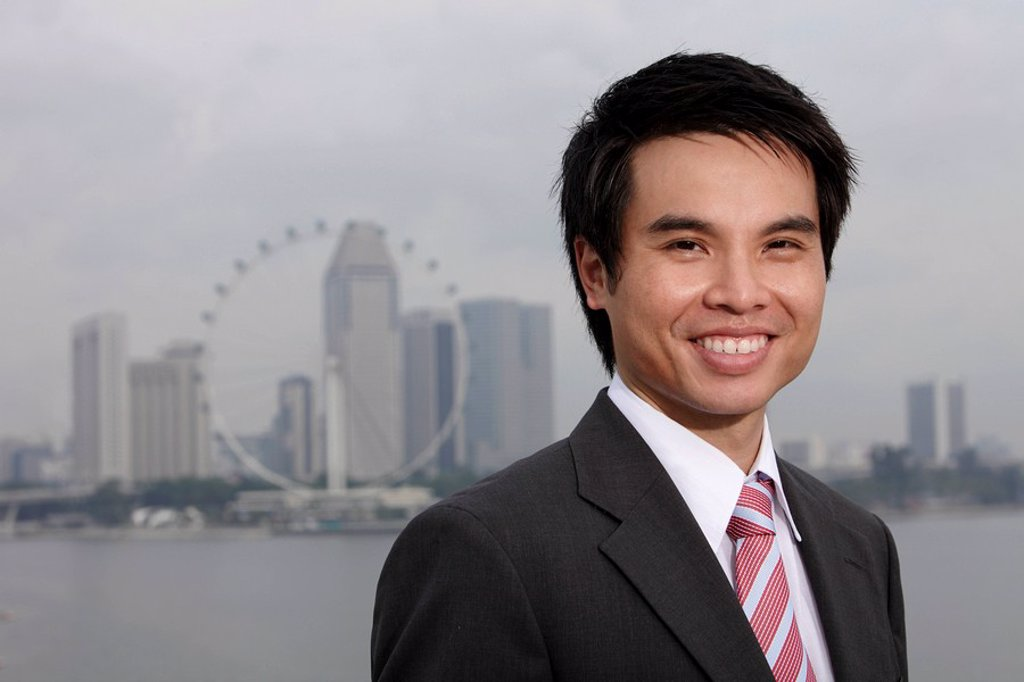 Chinese man in suit standing in front of city skyline, smiling : Stock Photo