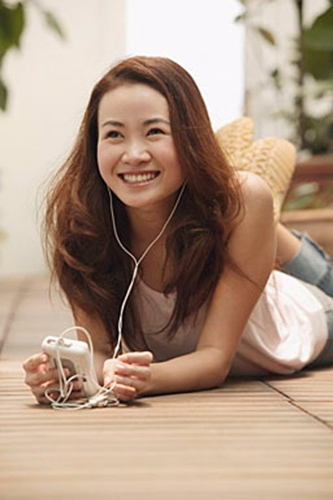 Young woman lying down, listening to music : Stock Photo
