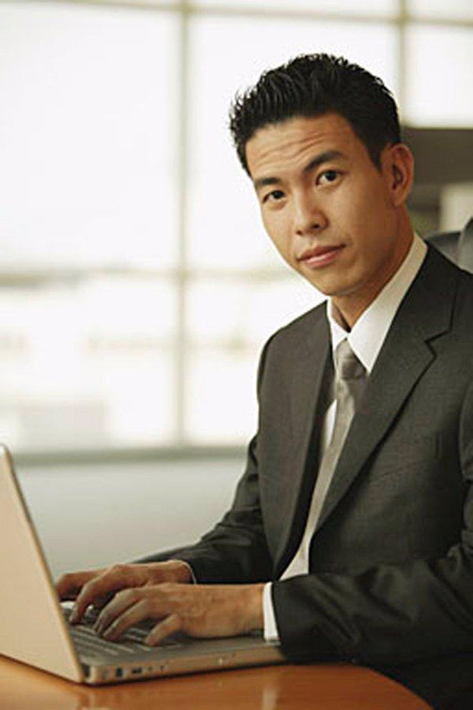 Young man looking at camera, using laptop : Stock Photo