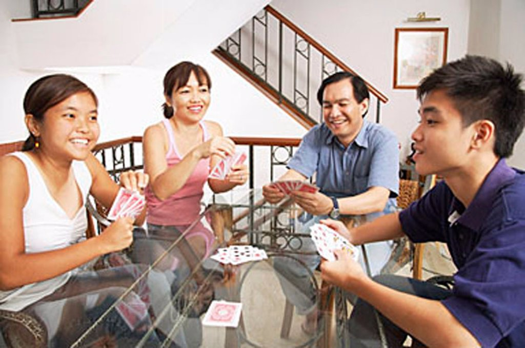 Family playing cards around table : Stock Photo