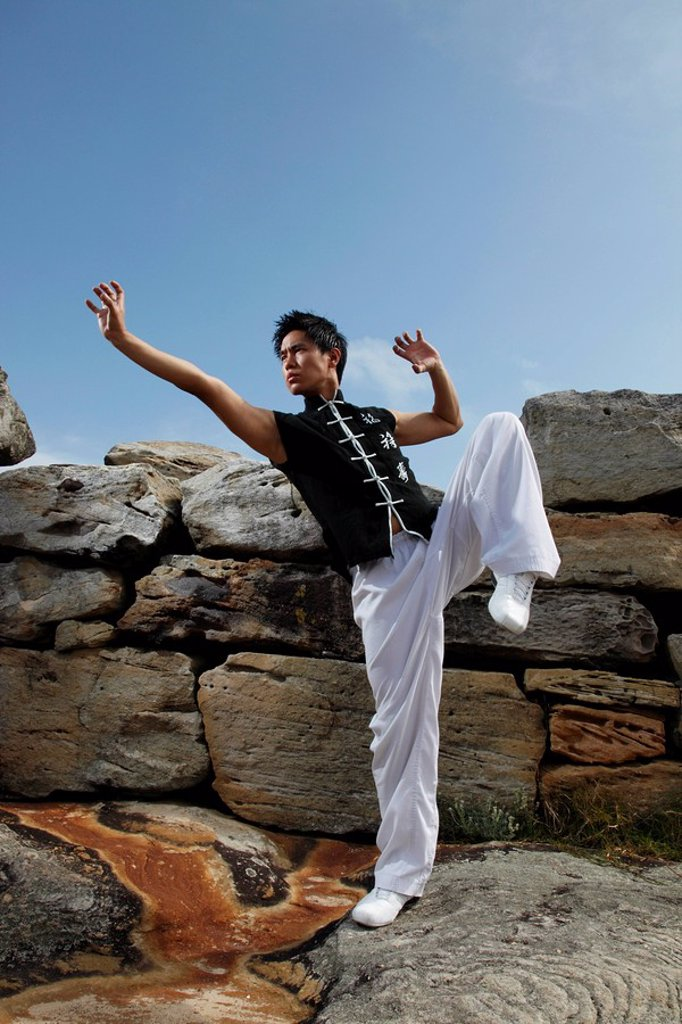 Chinese man doing martial arts on rocks : Stock Photo