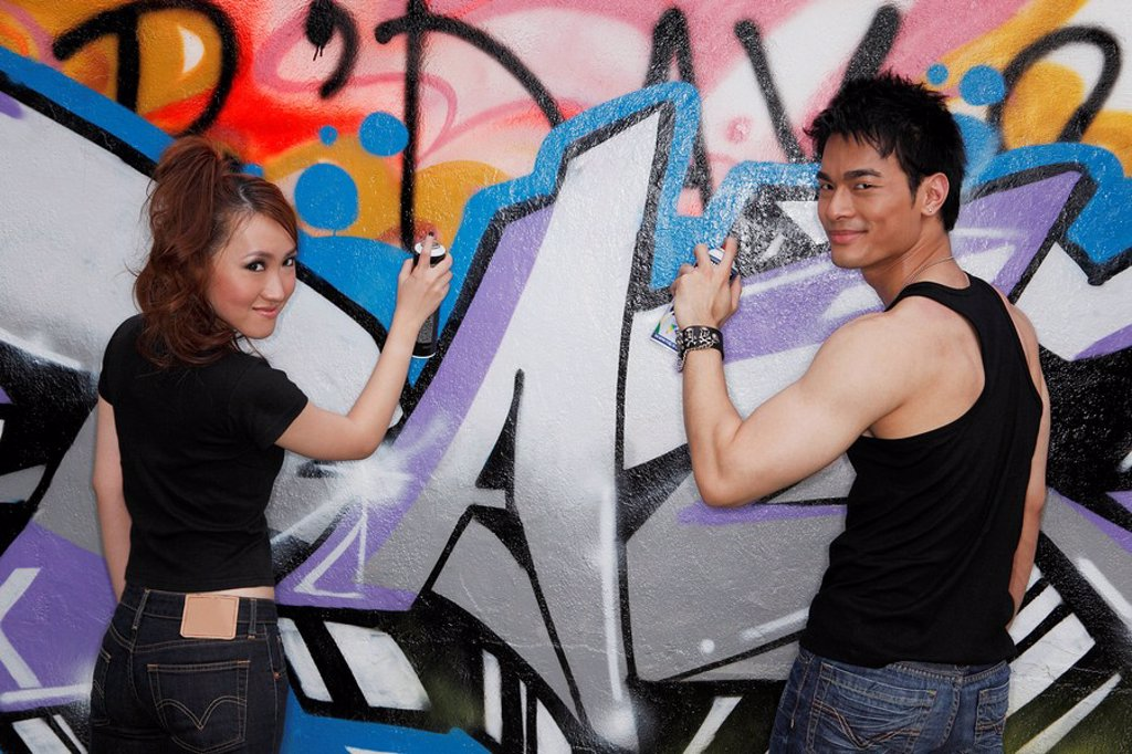 young couple spay painting graffiti on a wall together : Stock Photo