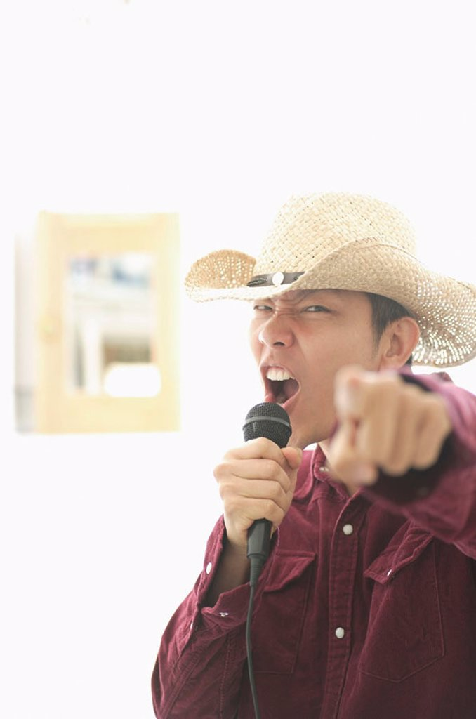 Man wearing hat, holding mike, singing and pointing at camera : Stock Photo