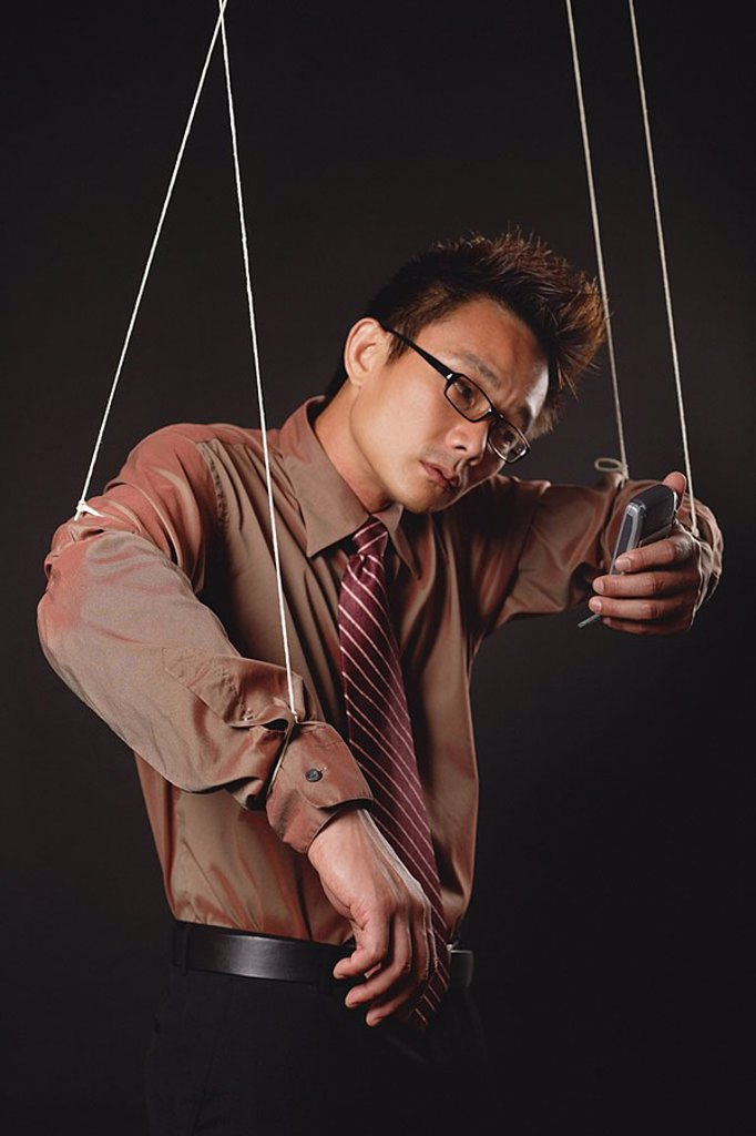 Stock Photo: 4065-13549 Man with marionette strings attached to his hands, holding mobile phone