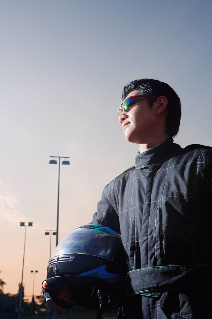 Stock Photo: 4065-13554 Racing driver, holding helmet, looking away