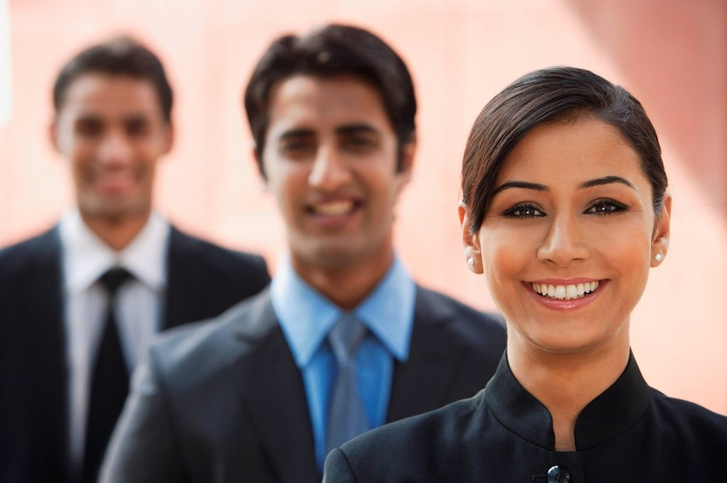 smiling businesswoman, two businessman in background : Stock Photo