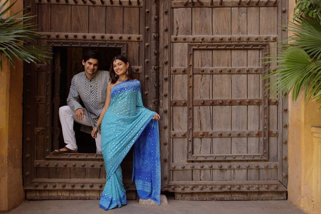 Stock Photo: 4065-13572 young couple posing at wooden doorway
