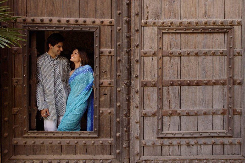 young couple at window in huge wooden doorway : Stock Photo