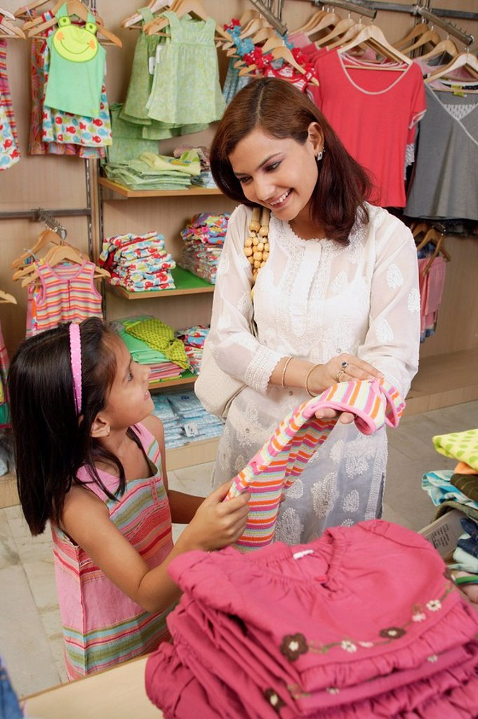 mother and daughter shopping for clothes : Stock Photo
