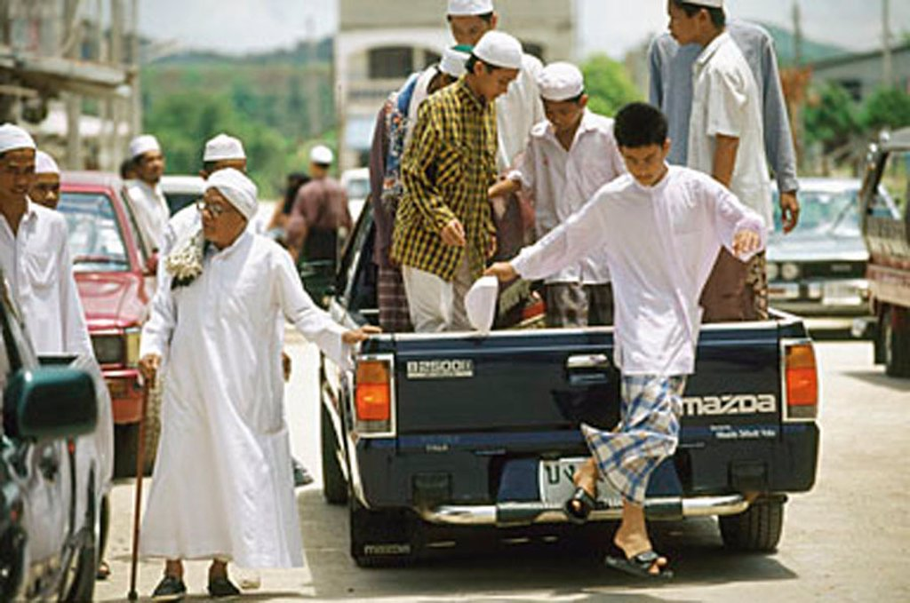 Thailand, Worshippers dress in traditional garb arrive for Friday prayers in the back of a pickup truck. : Stock Photo