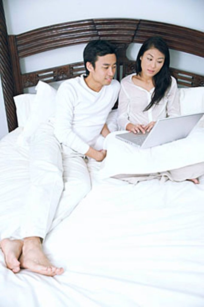 Couple lying in bed, using laptop : Stock Photo