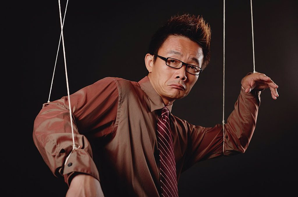 Stock Photo: 4065-14165 Man with marionette strings attached to his hands, looking at camera, frowning