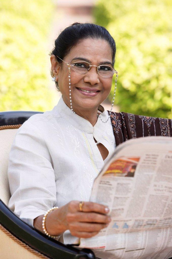 woman reading newspaper, wearing glasses, salwar kameez and shawl : Stock Photo