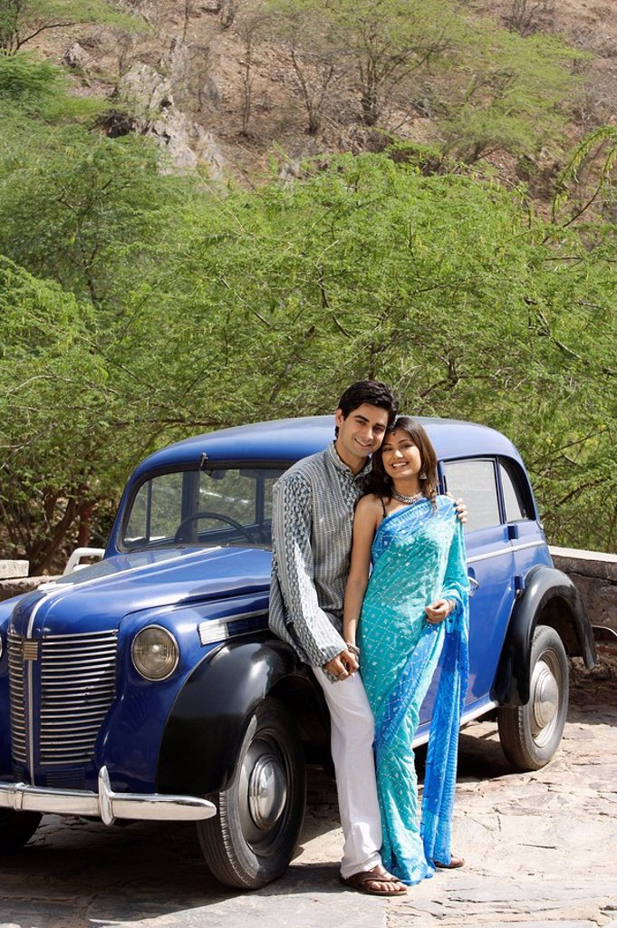 Stock Photo: 4065-14359 young couple standing in front of blue antique car