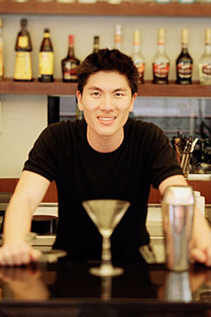Stock Photo: 4065-14414 Man behind bar counter, glass and mixer in front of him