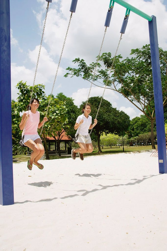 Young women on swings at playground : Stock Photo
