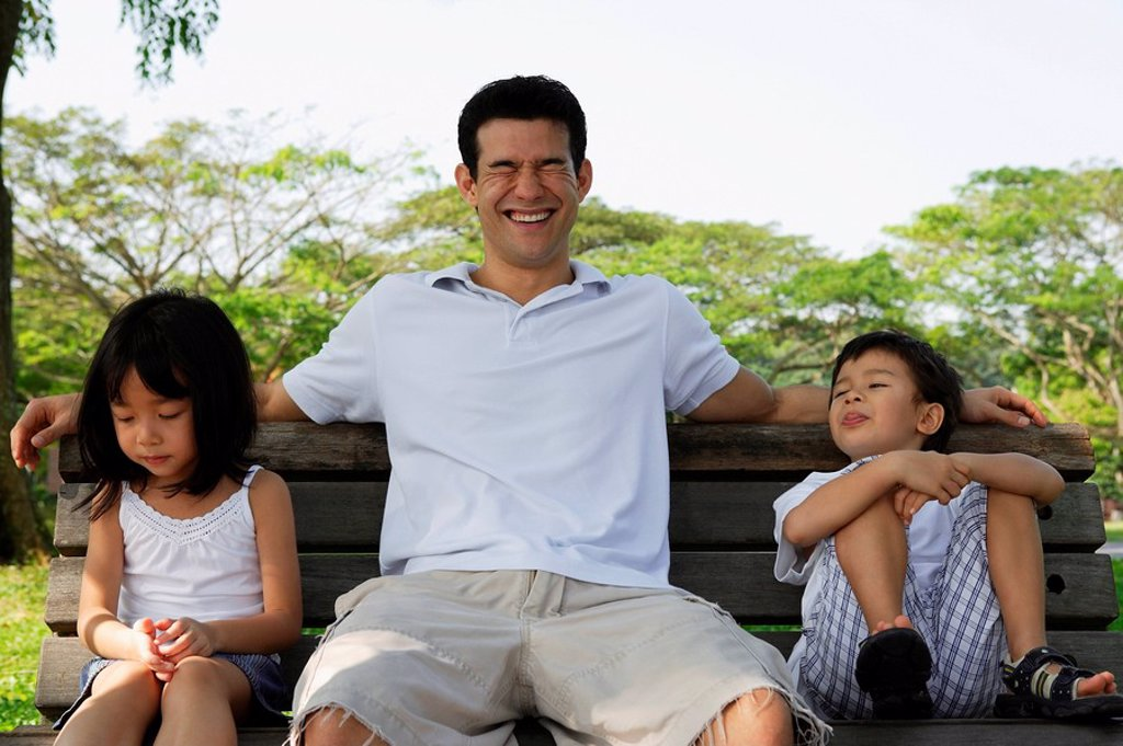 Father and children on park bench : Stock Photo