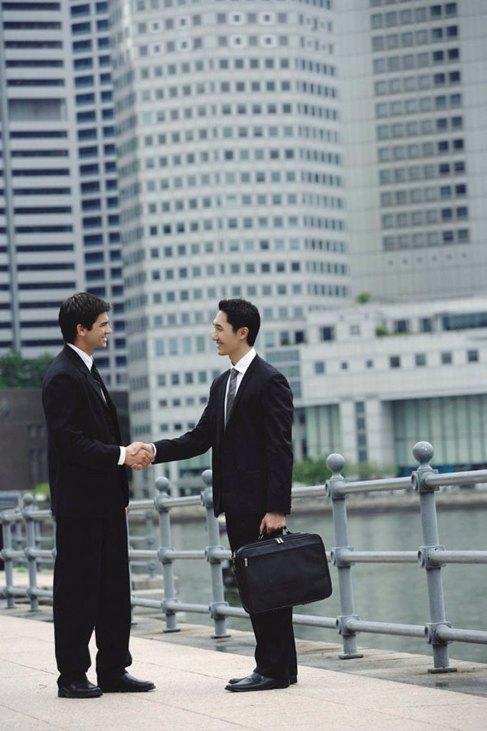 Stock Photo: 4065-1453 Two businessmen shaking hands, river and buildings in the background