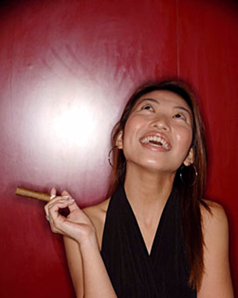 Woman with cigar, looking up. : Stock Photo