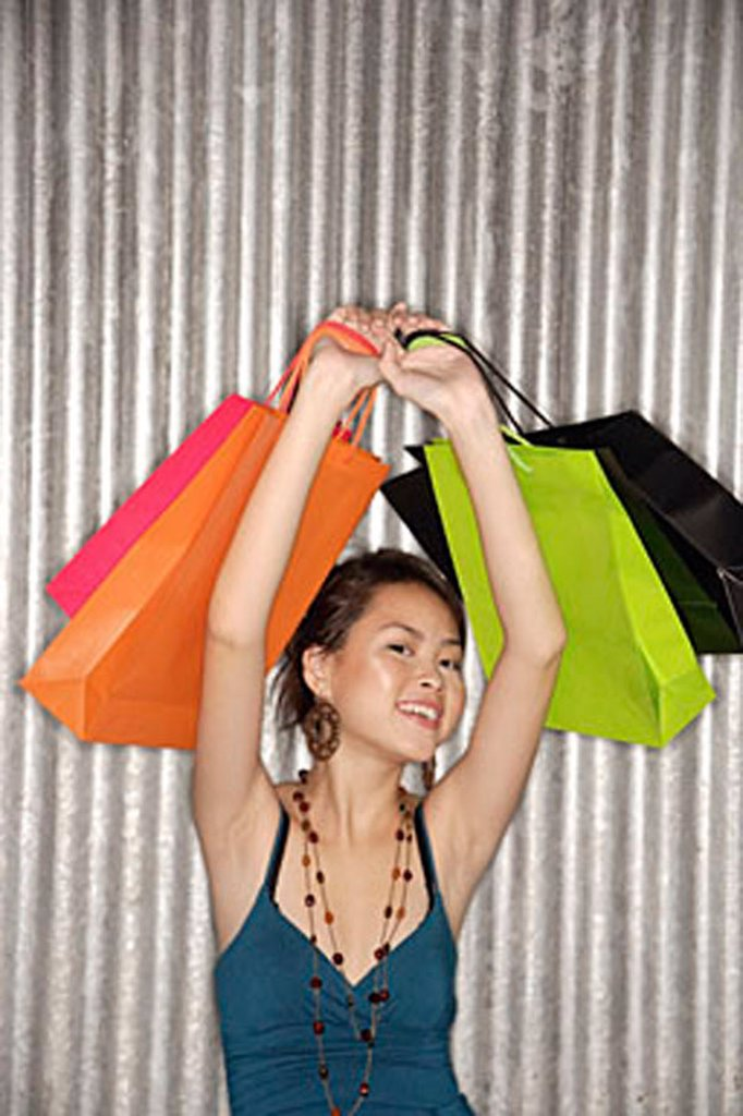 Young woman carrying shopping bags over her head, smiling at camera : Stock Photo