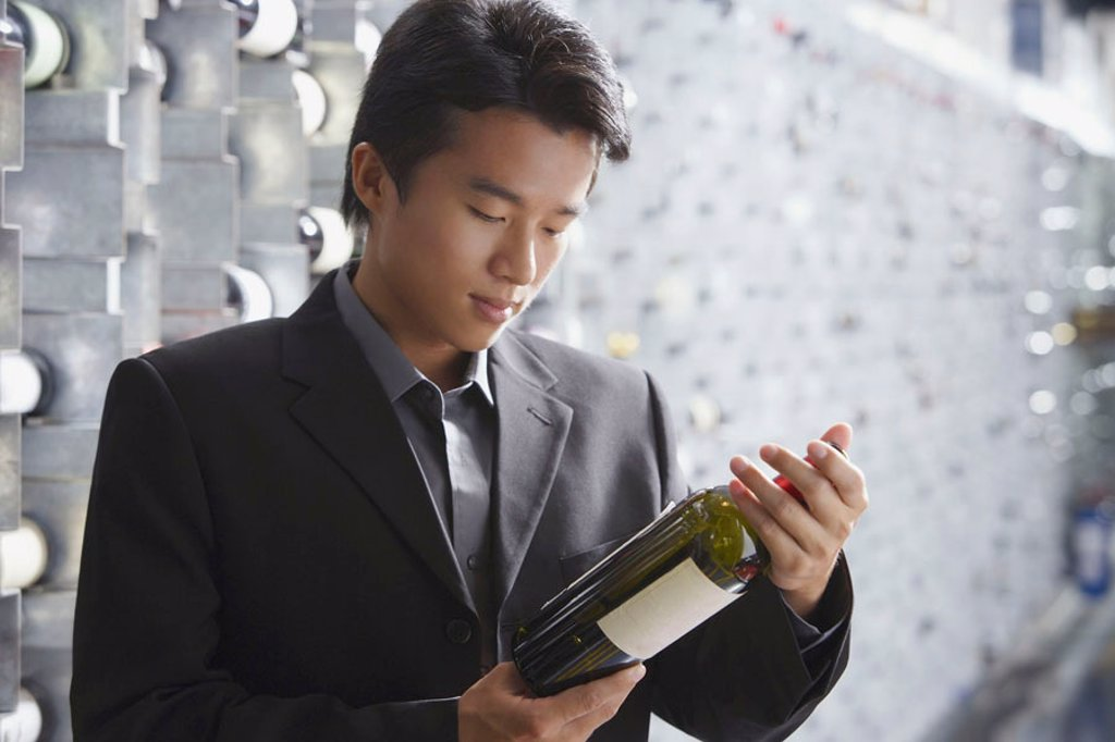 Man in wine cellar, looking at bottle of wine : Stock Photo