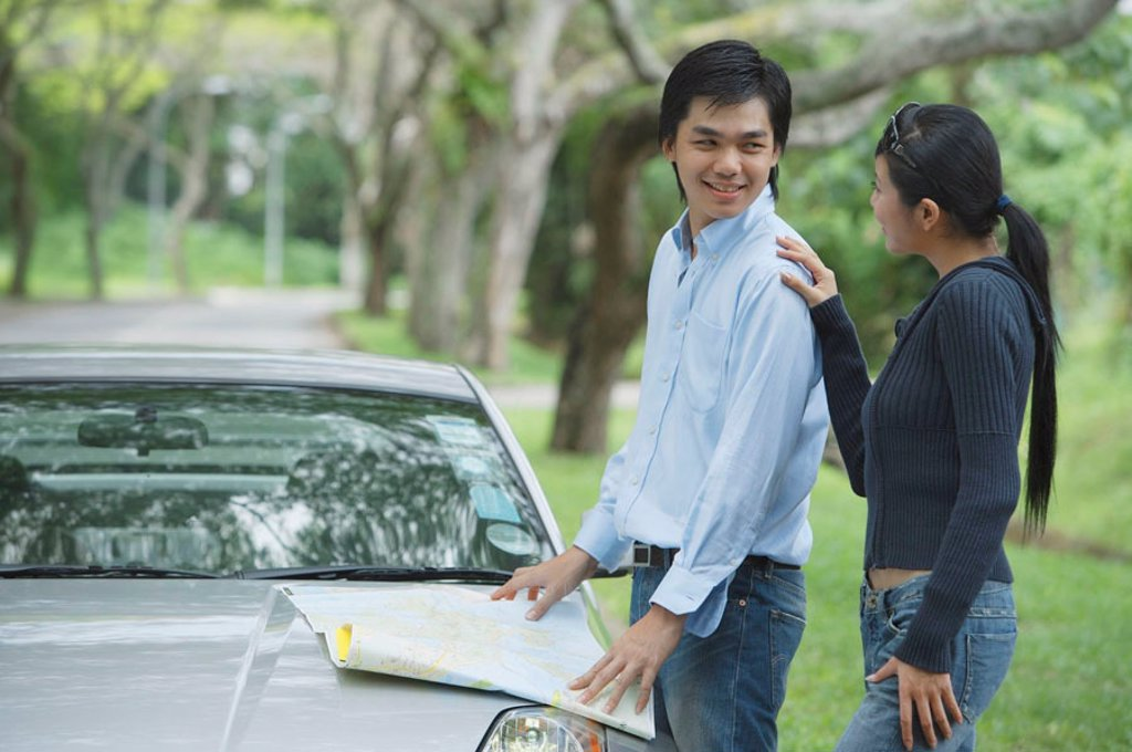 Stock Photo: 4065-1476 Couple next to car, man turning to look at woman