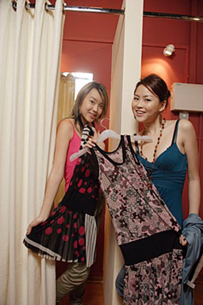 Stock Photo: 4065-14866 Two women trying on clothes at shop, looking at camera