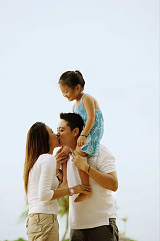 Stock Photo: 4065-14874 Couple kissing, daughter sitting on father´s shoulder