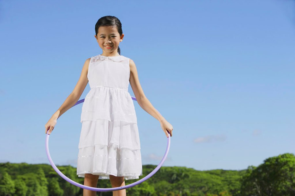 Stock Photo: 4065-14934 Girl in white dress, holding hoola hoop