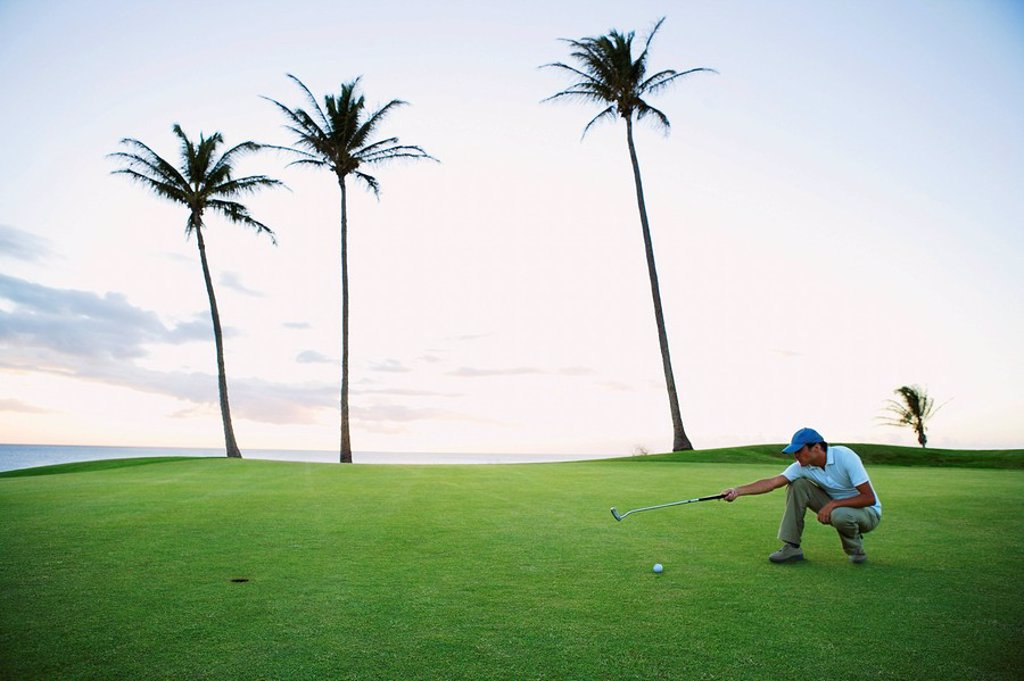man squatting on golf course, judging angle : Stock Photo