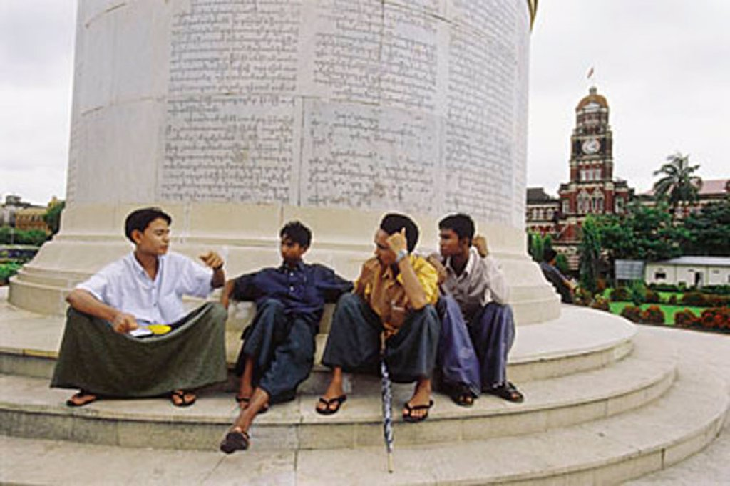 Myanmar (Burma), Yangon (Rangoon), Young men sitting at the base of the Independence Monument in Yangon. : Stock Photo
