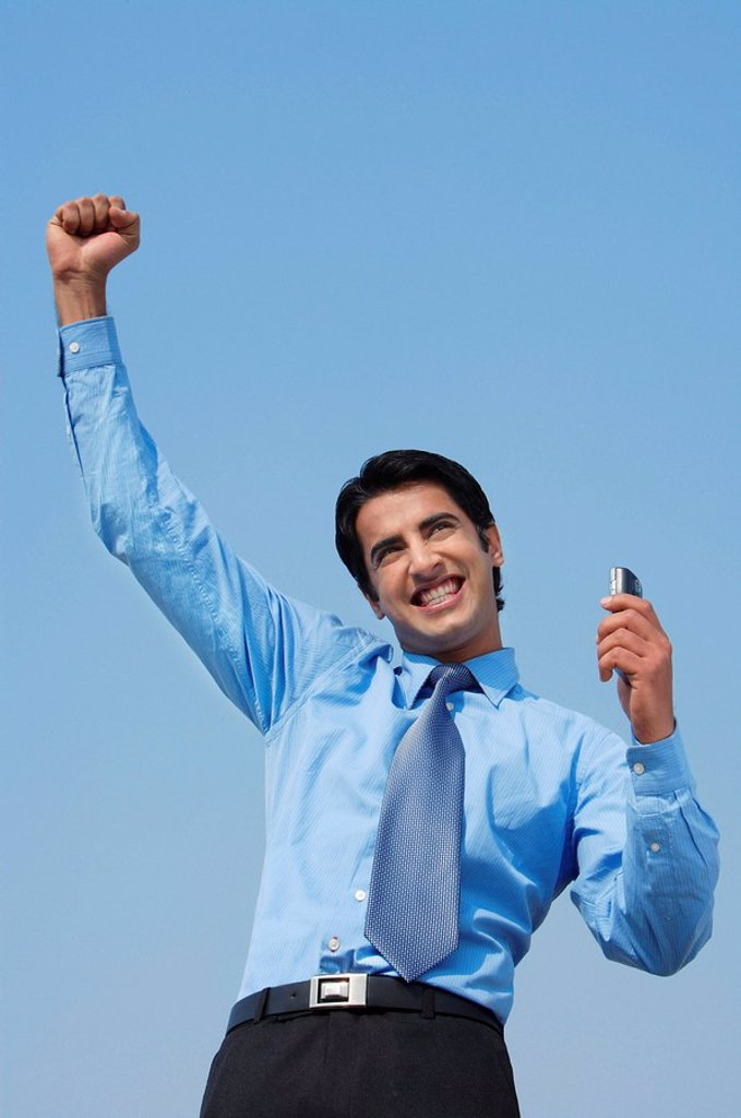 smiling business man with fist in air, phone in hand : Stock Photo