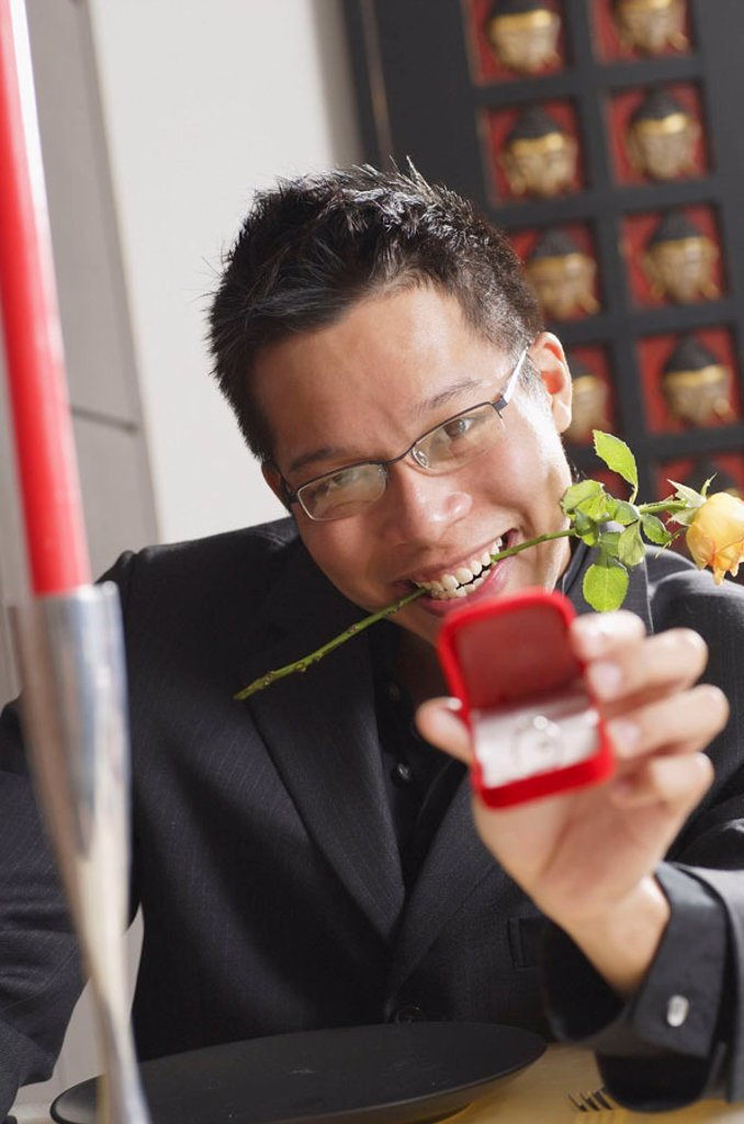 Man with rose stalk between teeth, holding ring box towards camera, smiling : Stock Photo