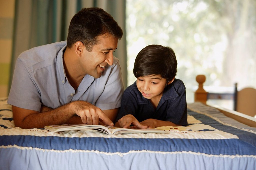 father and son reading book on bed : Stock Photo