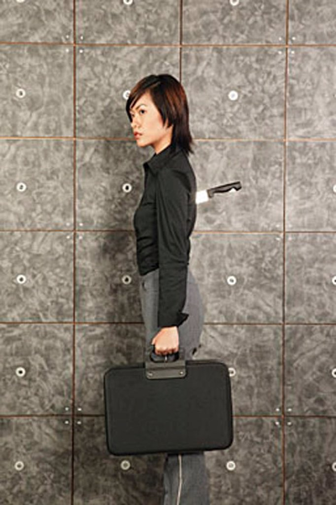 Female executive carrying briefcase, knife sticking out of her back : Stock Photo