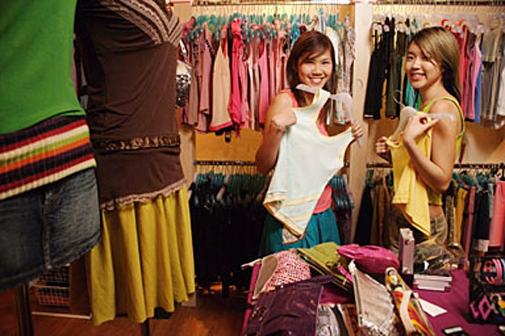 Two young women at clothes shop, holding up clothes, looking at camera : Stock Photo